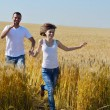 Happy couple in wheat field — Stock Photo #13123621