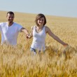 Happy couple in wheat field — Stock Photo #13149789