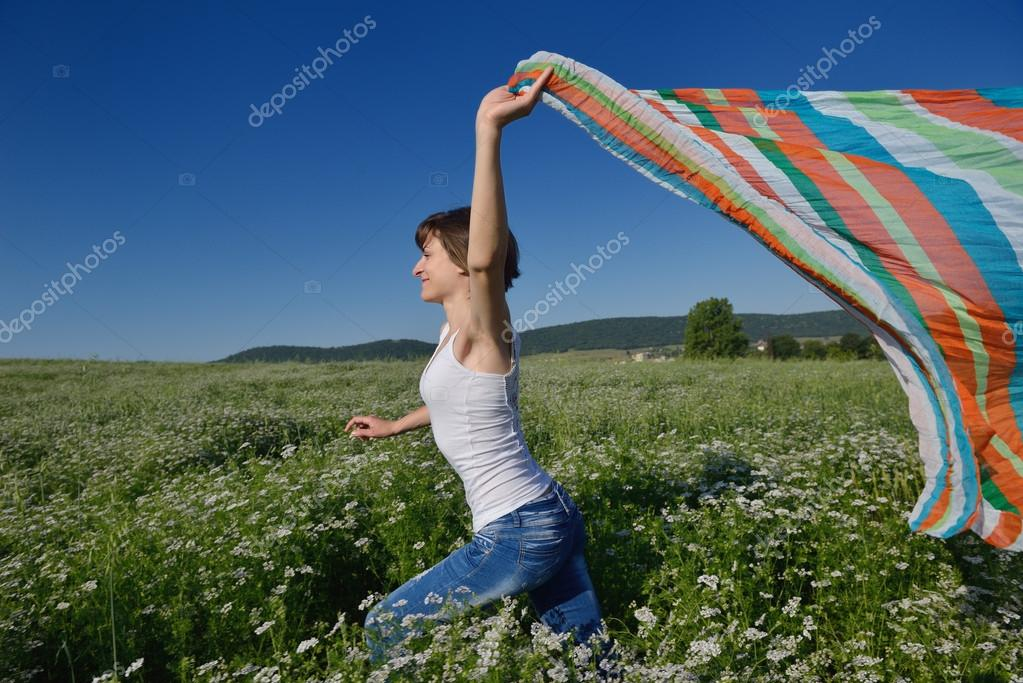 Young woman standing jumping and running  on a wheat field with blue sky in  background at summer day representing healthy life and agriculture concept — Stock Photo #13149486