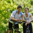 Happy couple riding bicycle outdoors — Stock Photo #13214132
