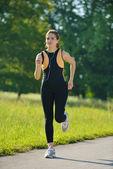 Jonge mooie vrouw op ochtend joggen in het park — Stockfoto