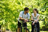 Happy couple riding bicycle outdoors — Stockfoto