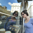 Woman in front of sweet store window — Stock Photo