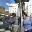 Woman in front of sweet store window — Stock Photo #13269564
