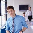Business man  on a meeting in offce with colleagues in backgroun — Stock Photo