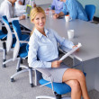 Business woman with her staff in background at office - Photo