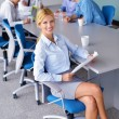 Business woman with her staff in background at office - Stock Photo