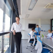 Business woman with her staff in background at office — Stock Photo #13270160