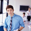 Business man on a meeting in offce with colleagues in backgroun — Stock Photo #14449161