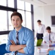 Business man on a meeting in offce with colleagues in backgroun — Stock Photo #14449291