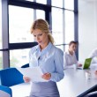 Business woman with her staff in background at office — Stock Photo #14449527
