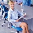 Business woman with her staff in background at office — Stok fotoğraf