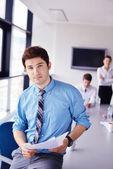 Hombre de negocios en una reunión en la oficina con colegas en backgroun — Foto de Stock