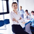 Business woman with her staff in background at office - Foto de Stock