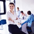 Business woman with her staff in background at office - Stockfoto