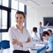 Business woman with her staff in background at office — Stock Photo #14450313
