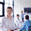 Business woman with her staff in background at office — Stock Photo #14450599