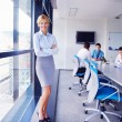 Business woman with her staff in background at office — Stockfoto