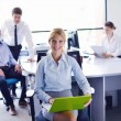 Business woman with her staff in background at office — Stock Photo #14456037