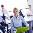 Business woman with her staff in background at office — Lizenzfreies Foto