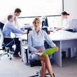Business woman with her staff in background at office — Stock Photo #14456305