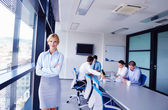 Mujer de negocios con su personal en segundo plano en la oficina — Foto de Stock