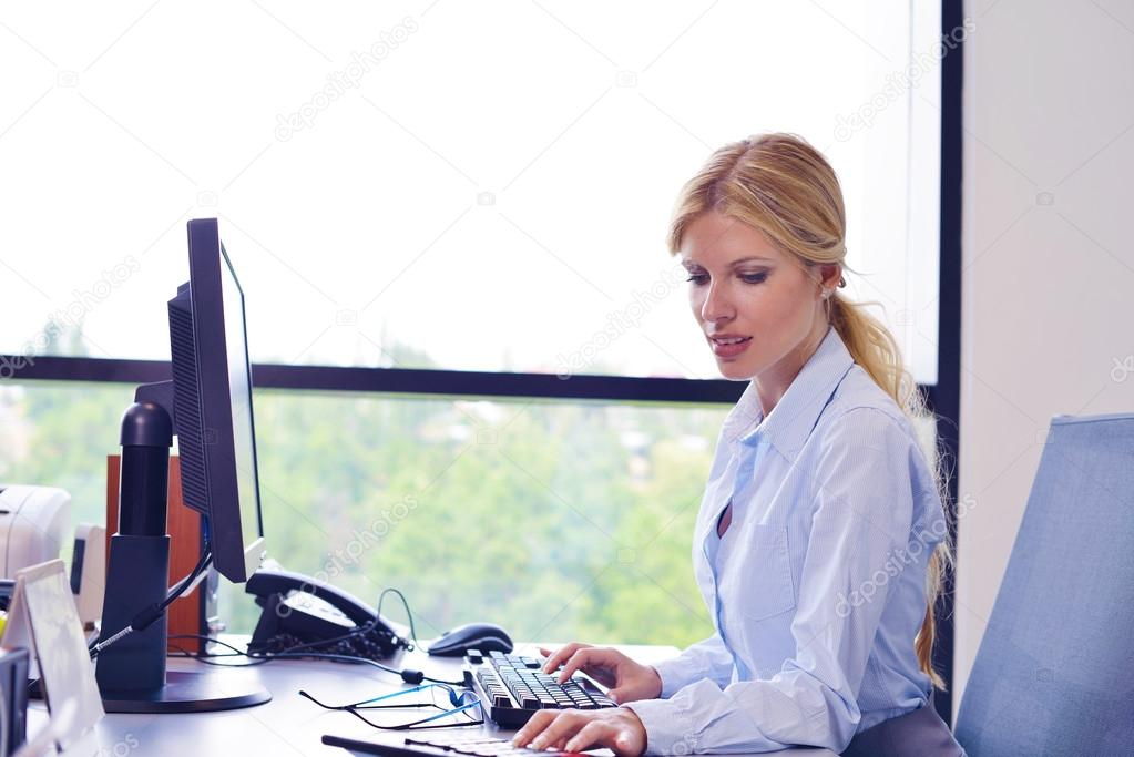 Portrait of a beautiful business woman working on her desk in an office environment. — Stock Photo #14452711