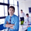 Business man on a meeting in offce with colleagues in backgroun — Stock Photo #15743091