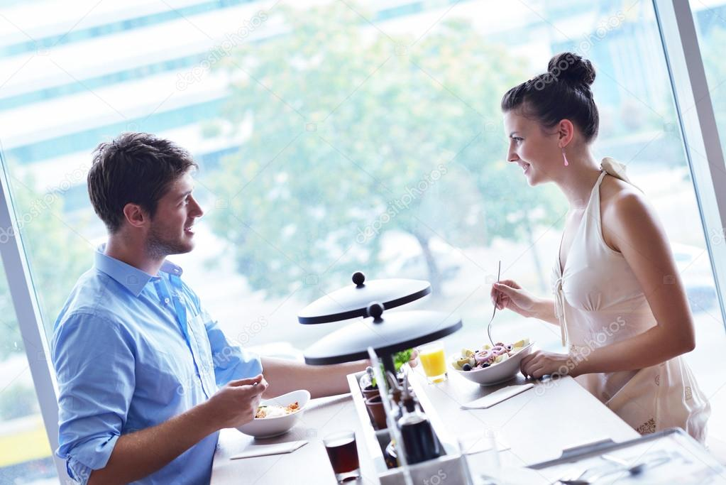A young couple sitting at a table and have lunch at an outdoor restaurant — Stock Photo #16801829