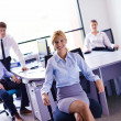 Business woman with her staff in background at office — Photo
