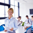 Business woman with her staff in background at office — Stock Photo #16941863