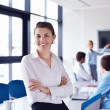 Business woman with her staff in background at office — Stock Photo #16941901