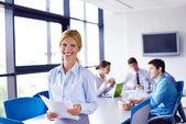 她在与工作人员在办公室背景的商界女强人 — 图库照片