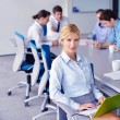 Business woman with her staff in background at office - Foto Stock