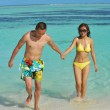 Asian couple enjoying summer on beach - Stockfoto