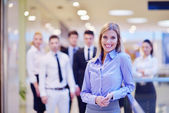 Business woman with her staff in background at office — Stock Photo
