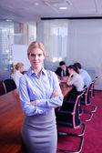 Business woman with her staff in background at office — Стоковое фото
