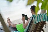 Uomo ralaxing e uso compresse in spiaggia — Foto Stock