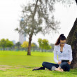 Beautiful young woman with  tablet in park — Stock Photo