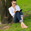 Young woman reading a book in the park — Stock Photo
