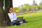 Woman with laptop in park — Stock Photo