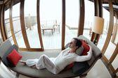 幸せな若い女性自宅でソファでリラックスします。 — ストック写真
