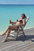 Beautiful young woman with a drink by the sea — Foto Stock