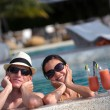 Happy young couple relax and take fresh drinks at poolside — Stock Photo #32724551