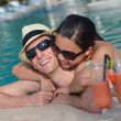 Young couple relax and take fresh drinks at poolside — Foto Stock