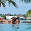 Young couple relax and take fresh drinks at poolside — ストック写真