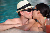 Happy young couple relax and take fresh drinks at poolside — Stock Photo