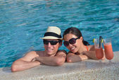 Young couple relax and take fresh drinks at poolside — Stock Photo