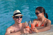 Young couple relax and toasting with fresh drinks at poolside — Stock Photo