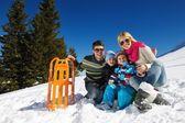 Family having fun on fresh snow at winter vacation — Stock Photo